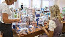 Работники школы разбирают школьные учебники. Архивное фото