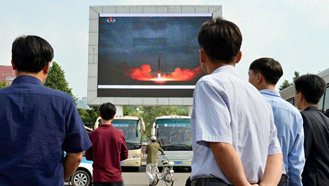 Жители КНДР смотрят репортаж о запуске баллистической ракеты Хвансон-12. 30 августа 2017