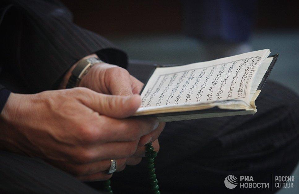 Книга в руках мусульманина, пришедшего в Соборную мечеть города Усть-Джегута в день праздника жертвоприношения. 1 сентября 2017