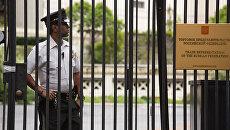 Сотрудник полиции стоит в оцеплении у здания российского торгового представительства в Вашингтоне