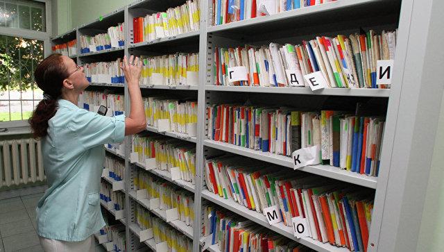 Сотрудник регистратуры работает с медицинскими картами пациентов в картотеке поликлиники №2 города Калининграда