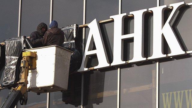 Рабочие завешивают вывеску с названием банка в Москве