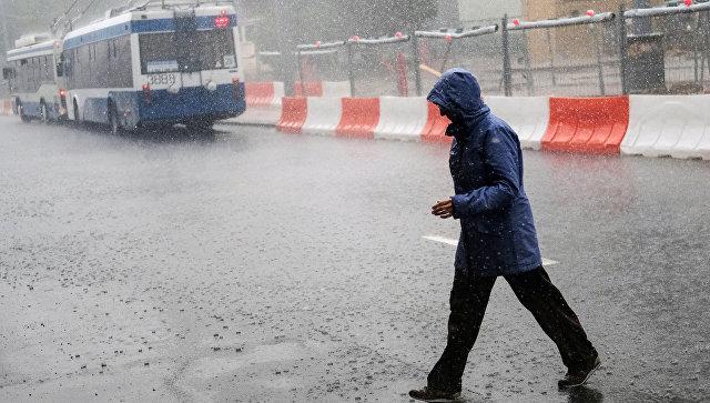 Прохожий во время ливня на одной из улиц Москвы. Архивное фото
