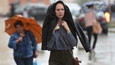 Прохожие идут на Смоленской площади во время дождя в Москве. Архивное фото