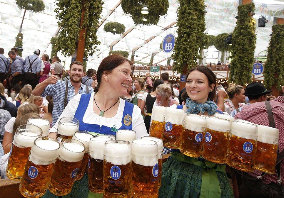 Официантки несут кружки с пивом на открытии фестиваля Октоберфест в Мюнхене