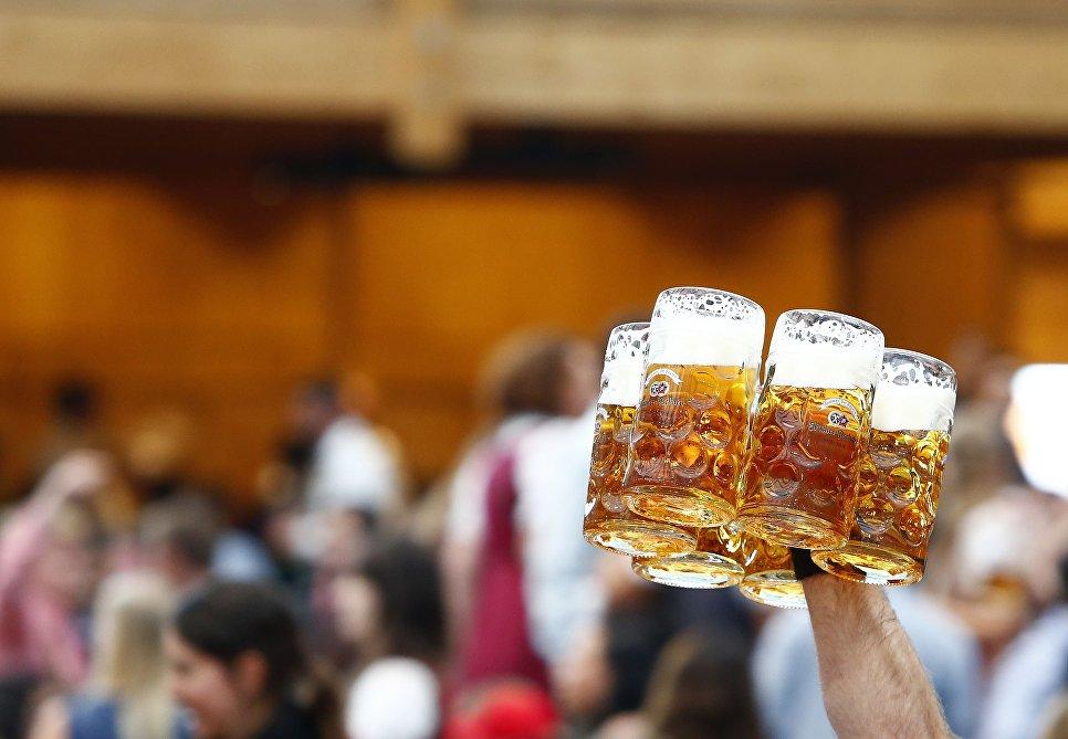 Официант несет кружки с пивом на открытии фестиваля Октоберфест в Мюнхене