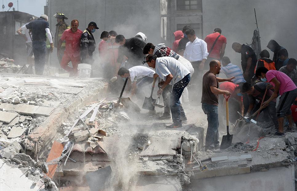 Люди помогают извлекать пострадавших из под обломков здания после землетрясения в Мехико