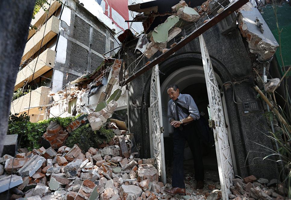 Мужчина выходит из здания, рухнушего после землетрясения, в Мехико. 19 сентября 2017