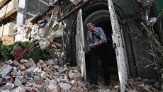 Мужчина выходит из здания, рухнушего после землетрясения, в Мехико. Архивное фото