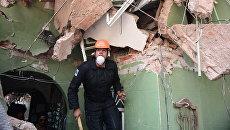 Спасатель ищет выживших после землетрясения в Мехико. Архивное фото