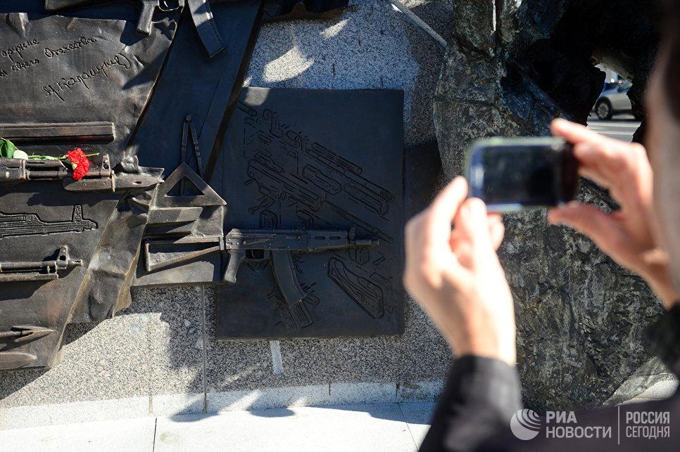 Прохожий фотографирует фрагмент памятника оружейнику Михаилу Калашникову в Москве