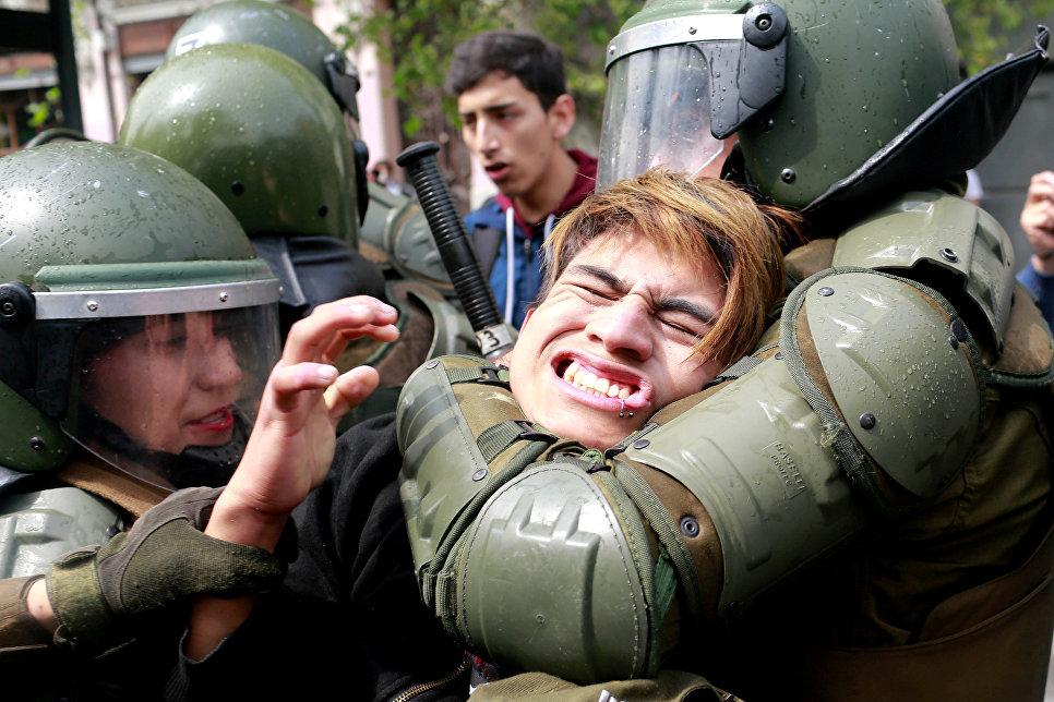 Задержание демонстранта во время студенческого протеста в Чили.