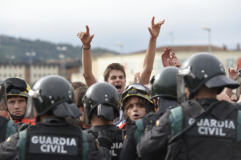 Пожарные удерживают людей от столновения с испанскими офицерами гражданской полиции в Каталонии. 1 октября 2017