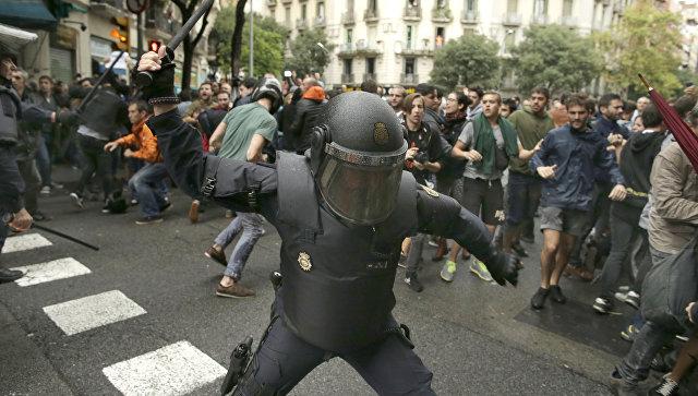 Испанская полиция угрожает дубинкой потенциальным избирателям в Барселоне, Испания. 1 октября 2017