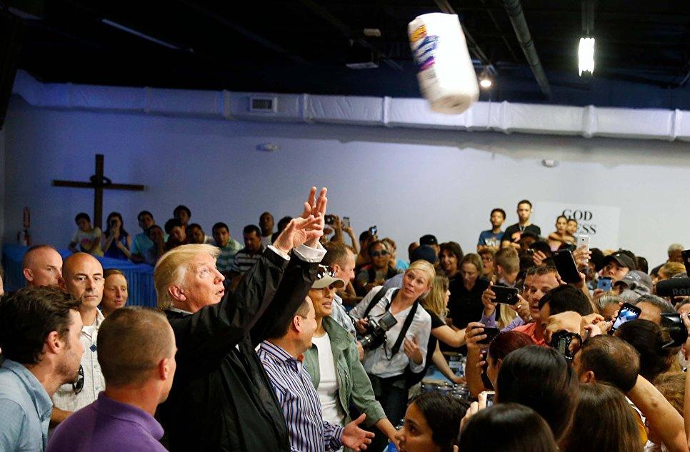 Президент США Дональд Трамп бросает рулоны бумажных полотенец в толпу местных жителей, пострадавших от урагана Мария в Сан-Хуане, Пуэрто-Рико, США