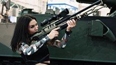 Девушка осматривает винтовку на выставке Оружие и безопасность в Киеве