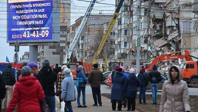 Прохожие наблюдают за ходом работ служб МЧС РФ по расчистке завалов частично обрушившегося жилого панельного дома на Удмуртской улице в Ижевске. 10 ноября 2017