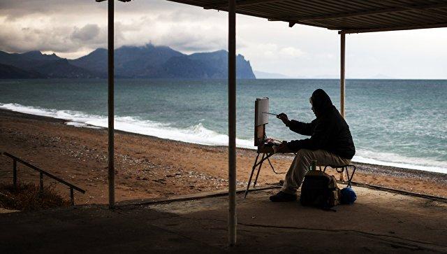 Художник рисует на одном из пляжей Севастополя. Архивное фото