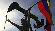 Мужчина с флагом Венесуэлы перед зданием компании PDVSA в Каракасе. Архивное фото
