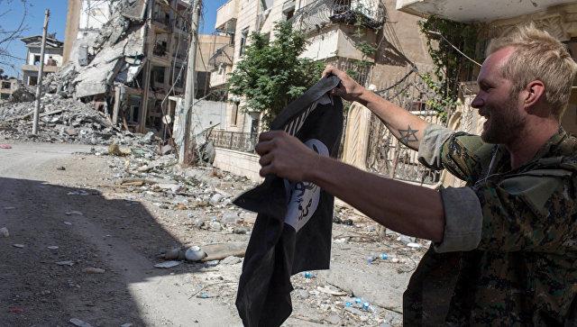 Мужчина в военной форме держит флаг ИГ (террористическая организация, запрещена в РФ) в Ракке