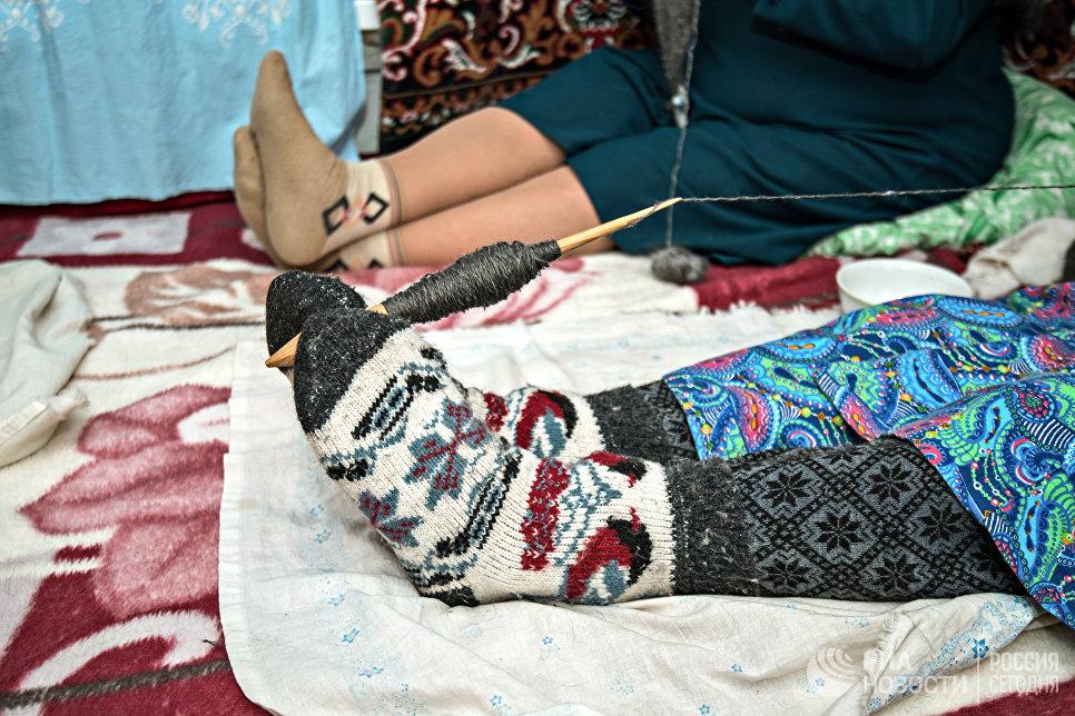 Для удобства по привычке Шагидэ эби держит веретено ногами. На ногах обязательно теплые носки, связанные своими руками.