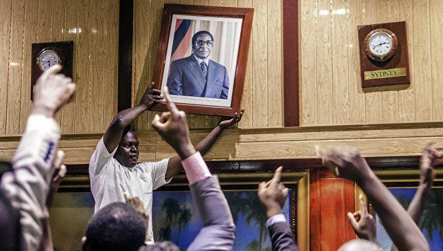 Мужчина снимает со стены портрет бывшего президента Зимбабве Роберта Мугабе в Международном конференц-центре, где заседает парламент, Хараре. 21 ноября 2017