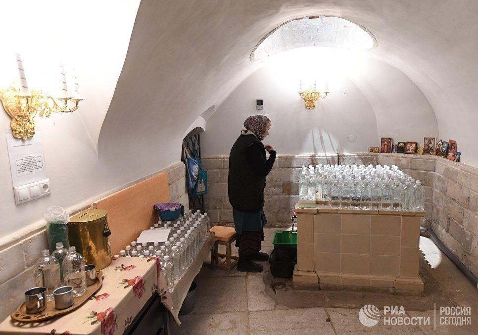 Матушка у источника со святой водой в подземной Церкви Константина и Елены на территории Ново-Иерусалимского мужского монастыря