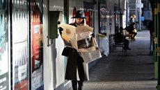 Женщина читает газету в метро Лондона