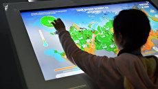Ребенок у интерактивного стенда на выставке Россия, устремленная в будущее в Центральном Манеже в Москве