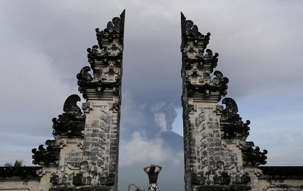 Турист наблюдает за извержением вулкана Агунг на острове Бали в Индонезии