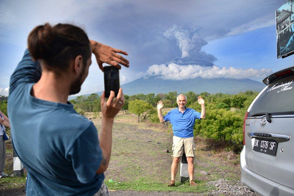 Туристы фотографируются на фоне извержения вулкана Агунг на острове Бали в Индонезии
