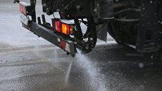 Снегоуборочная машина обрабатывает улицу противогололедным средством. Архивное фото