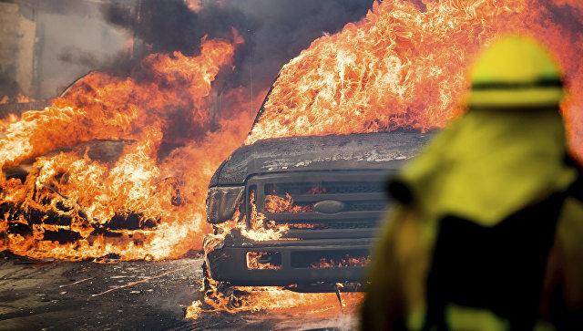 Автомобили, охваченные пламенем от лесного пожара, в городе Вентура в Калифорнии, США. 5 декабря 2017