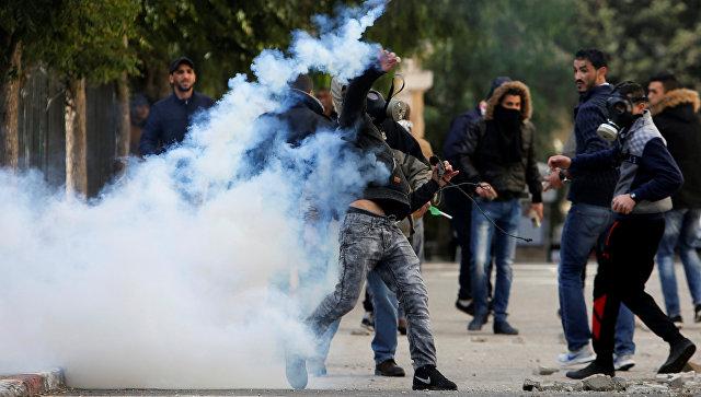 Палестинский протестующий бросает баллон со слезоточивым газом в сторону израильских военныз во время столкновений в Вифлееме на Западном берегу