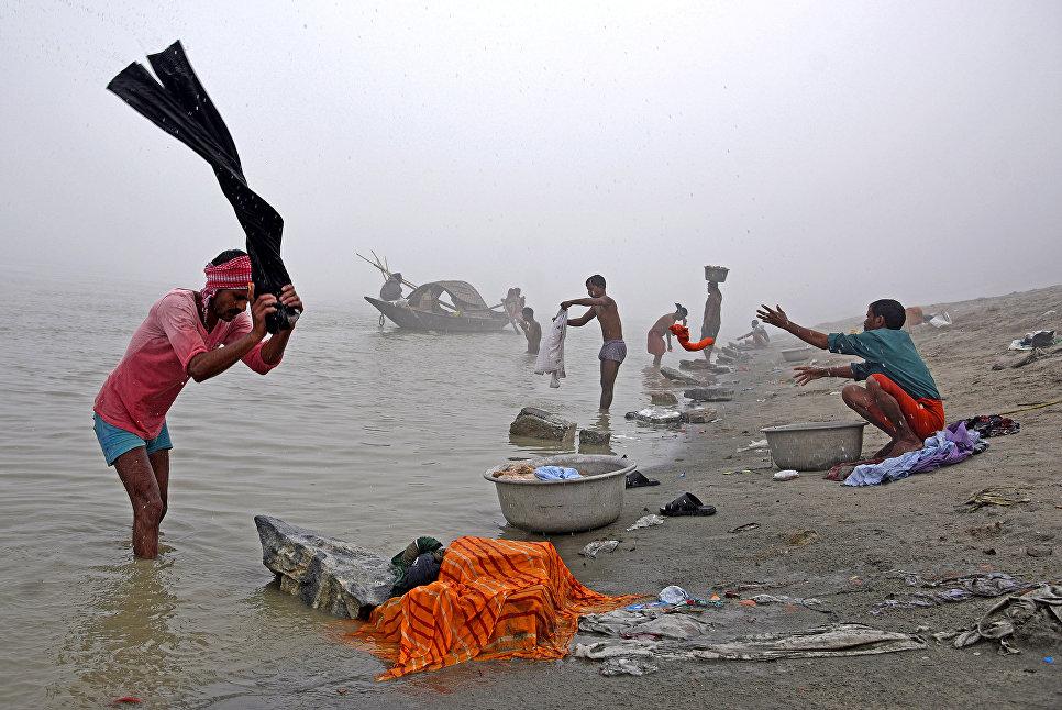 Люди стирают одежду на берегу реки Брахмапутры в Индии. 4 декабря 2017 года