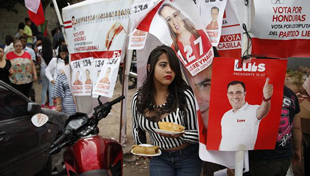 Женщина рядом с агитационным плакатом в поддрежку кандидата в президенты от Либеральной партии Луиса Селайя. Архивное фото