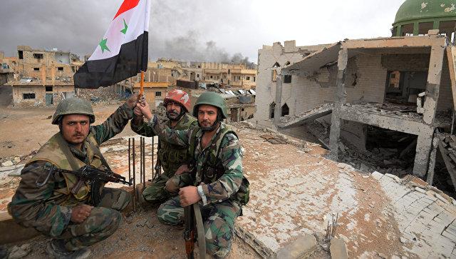 Солдаты сирийской армии (САА) с флагом Сирии радуются освобождению Пальмиры. Архивное фото