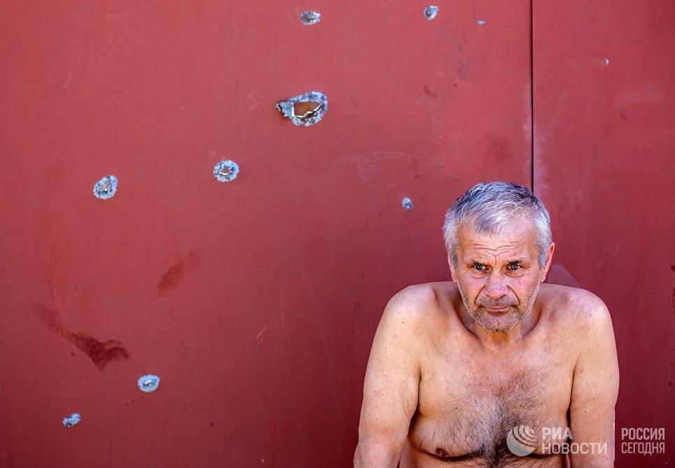 Мужчина сидит у ворот своего дома, разрушенного в результате ночного артобстрела со стороны украинских военных на окраине Славянска