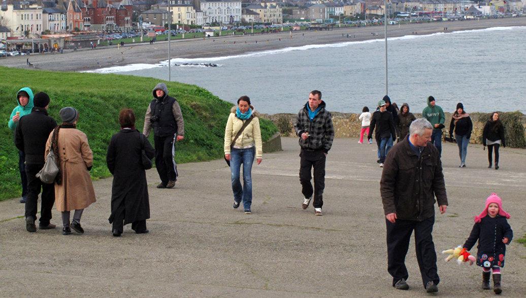 Люди прогуливаются вдоль обрыва Брей-Грейстоун над Ирландским морем возле Дублина