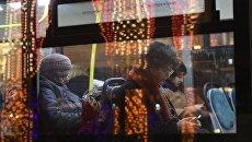Пассажиры в салоне автобуса, проезжающего мимо Театральной площади в Москве. Архивное фото