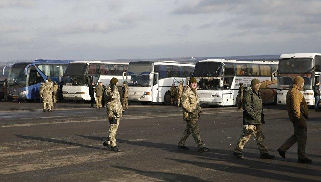 Украинские военные рядом с автобусомами, перевозящим военнопленных ДНР и ЛНР к месту обмена в районе города Бахмут в Донецкой области. 27 декабря 2017