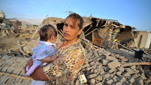 Женщина перед домом. поврежденным землетрясением силой 7,1 баллов, поразившем побережье южного Перу. 14 января 2018