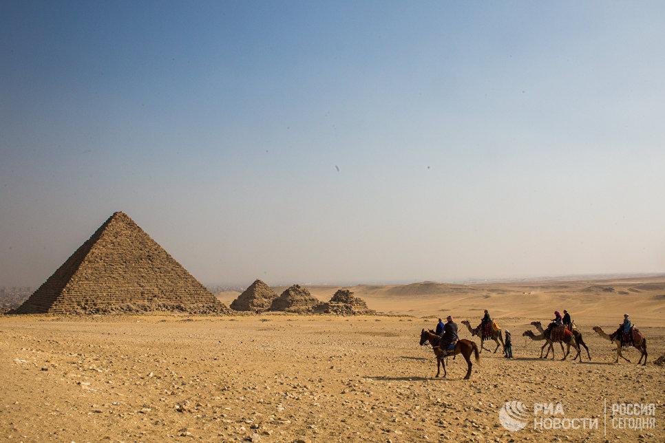 Группа туристов верхом на лошадях и верблюдах во время экскурсии к древнеегипетским пирамидам в Эль-Гизе, пригороде Каира. Слева: пирамида Микерина (Менкаура)