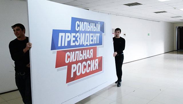 Рабочие несут плакат в избирательный штаб действующего президента РФ Владимира Путина. Архивное фото