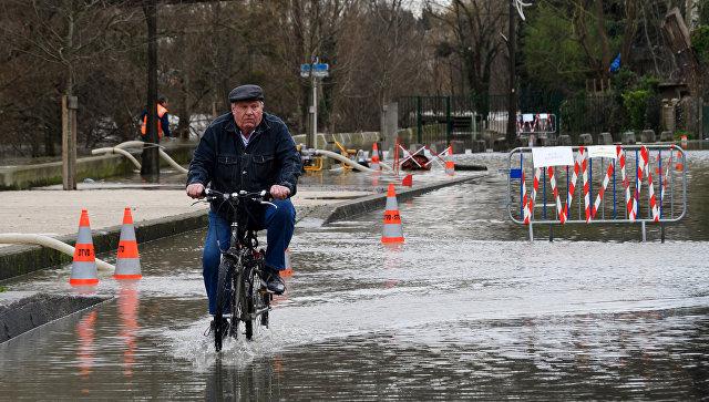 Местный житель едет на велосипеде по одной из затопленных улиц в Париже, из-за прошедших ливневых дождей. Архивное фото