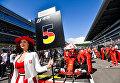 Девушка держит табличку с номером места гонщика команды Феррари Себатьяна Феттеля на трассе перед гонкой на российском этапе чемпионата мира по кольцевым автогонкам в классе Формула-1
