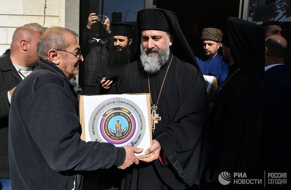 Участники межконфессиональной делегации религиозных деятелей из России во время раздачи гуманитарной помощи для сирийских беженцев в греко-католической церкви в ливанском городе Захия
