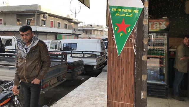 Флаг курдских сил самообороны (YPJ) на центральной улице города Африн, Сирия