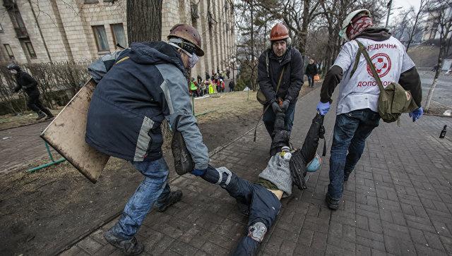 Сторонники оппозиции несут раненного во время столкновений с сотрудниками правопорядка на улице Институской в Киеве