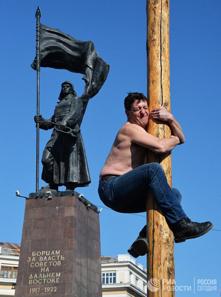 Участник народных забав на праздничной ярмарке Широкой Масленицы на центральной площади Владивостока. 17 февраля 2018